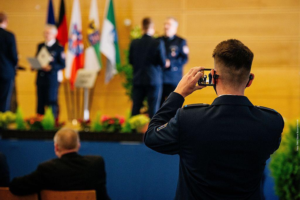Polizeischüler macht ein Bild mit seinem Handy