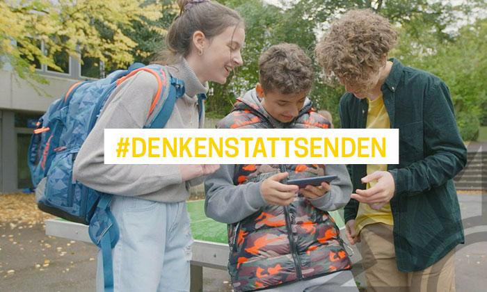 Bild zeigt drei Jugendliche, welche auf ein Handy schauen und lachen