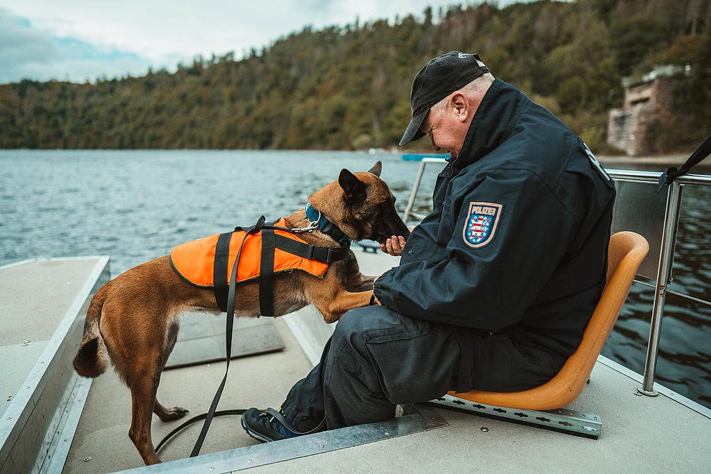 Polizeihund mit seinem Diensthundführer auf einem Boot im Wasser